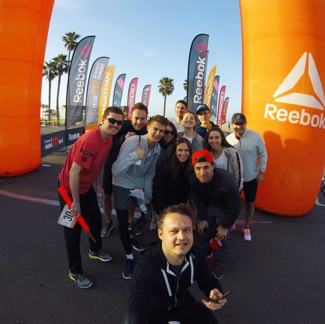 A team of Reebok employees stand together at the finish line happy of their achievement. team, Reebok, happy, proud, achievement, determination