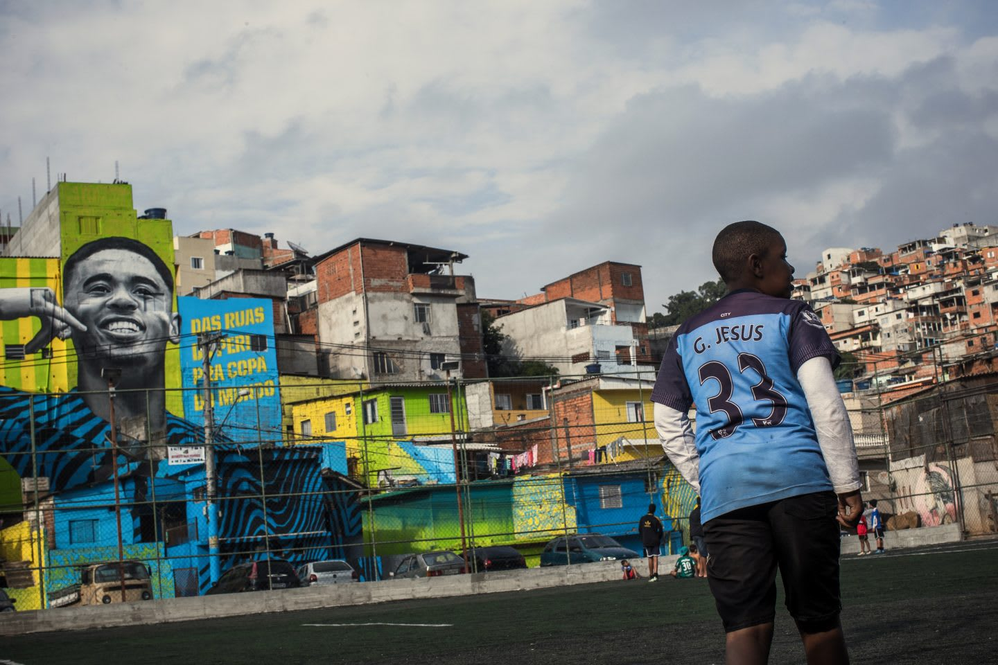 A young child walks across a football pitch in his neighborhood in Brazil beside a mural of Gabriel Jesus. Gabriel Jesus, soccer, street art, mural, brazil