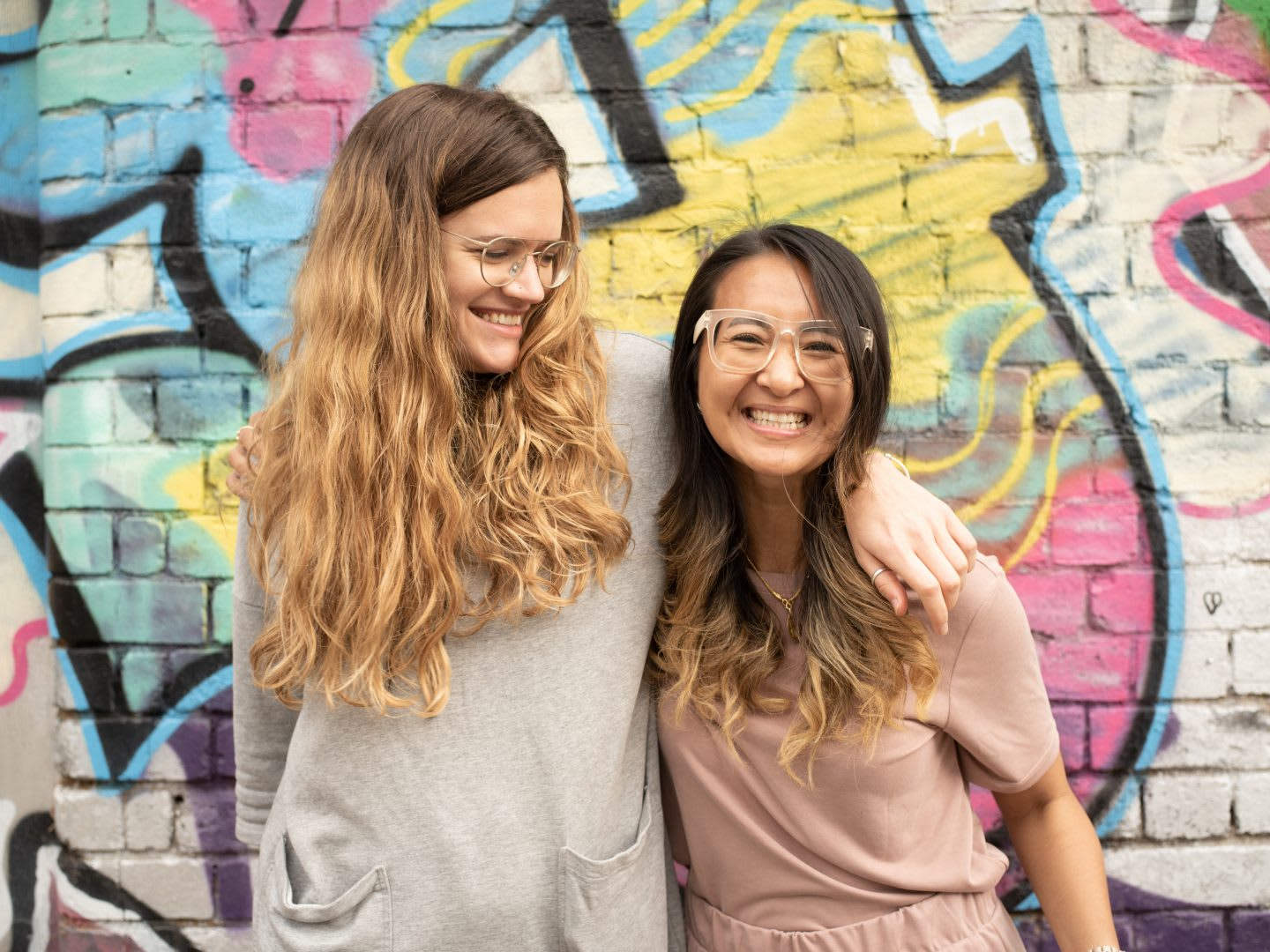 Two friends wrap an arm around each other smiling. friends, smiling, happy, graffiti