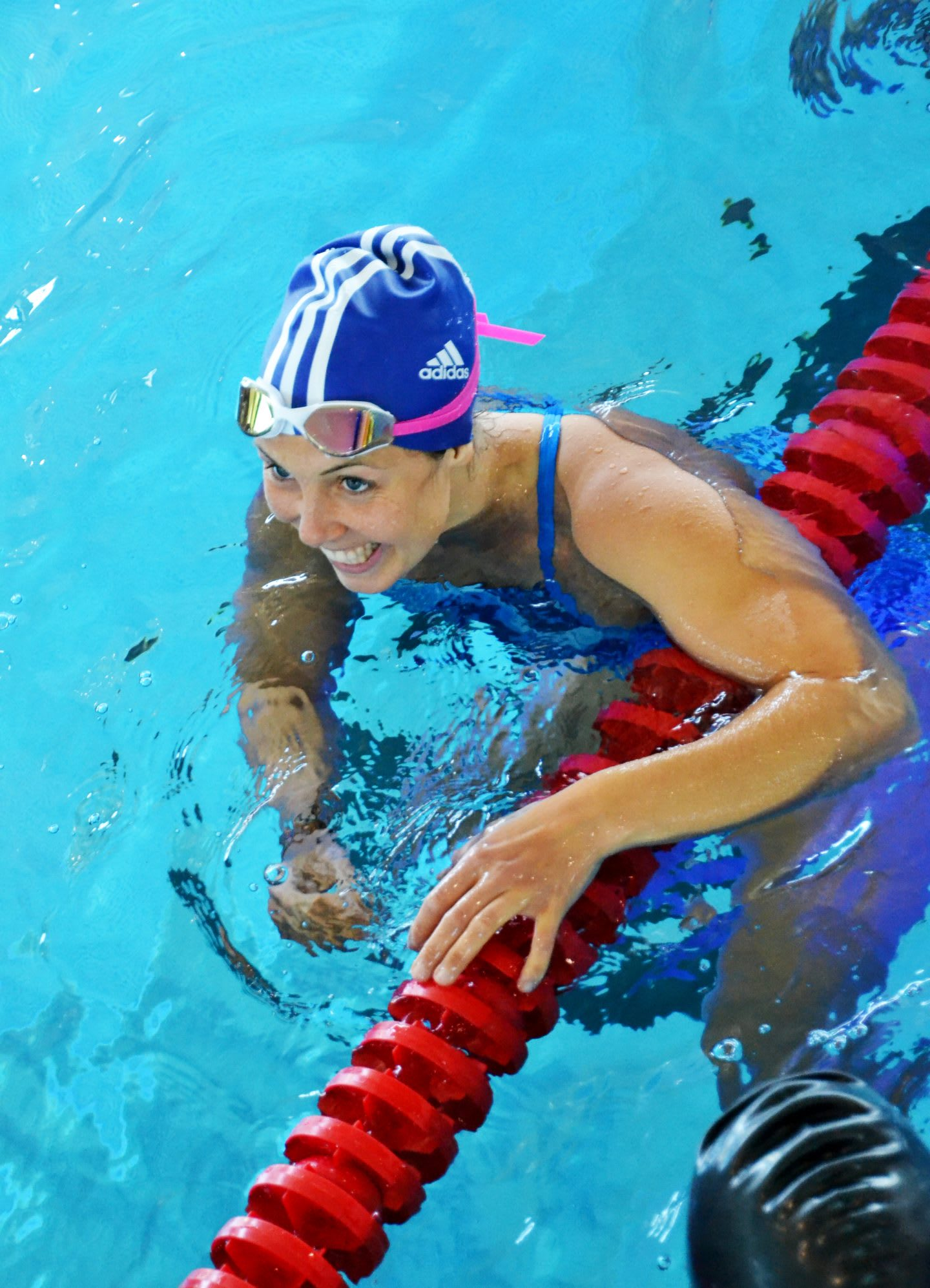 A woman smiles happily in a swimming pool. swim, swimming, swimmer, happy, smiling, achievement, accomplishment