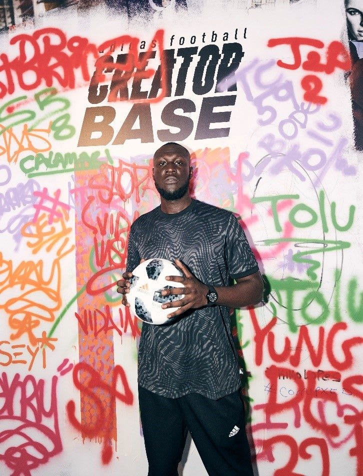 London Rapper Stormzy stands in front of a graffiti wall holding the adidas world cup ball. adidas, stormzy, rapper, music, world cup, london