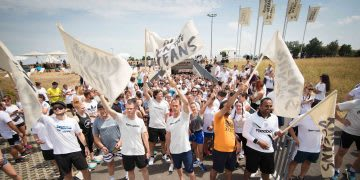 A group of adidas employess begin their run for the oceans holding flags. parley, running, run, oceans, team, movement