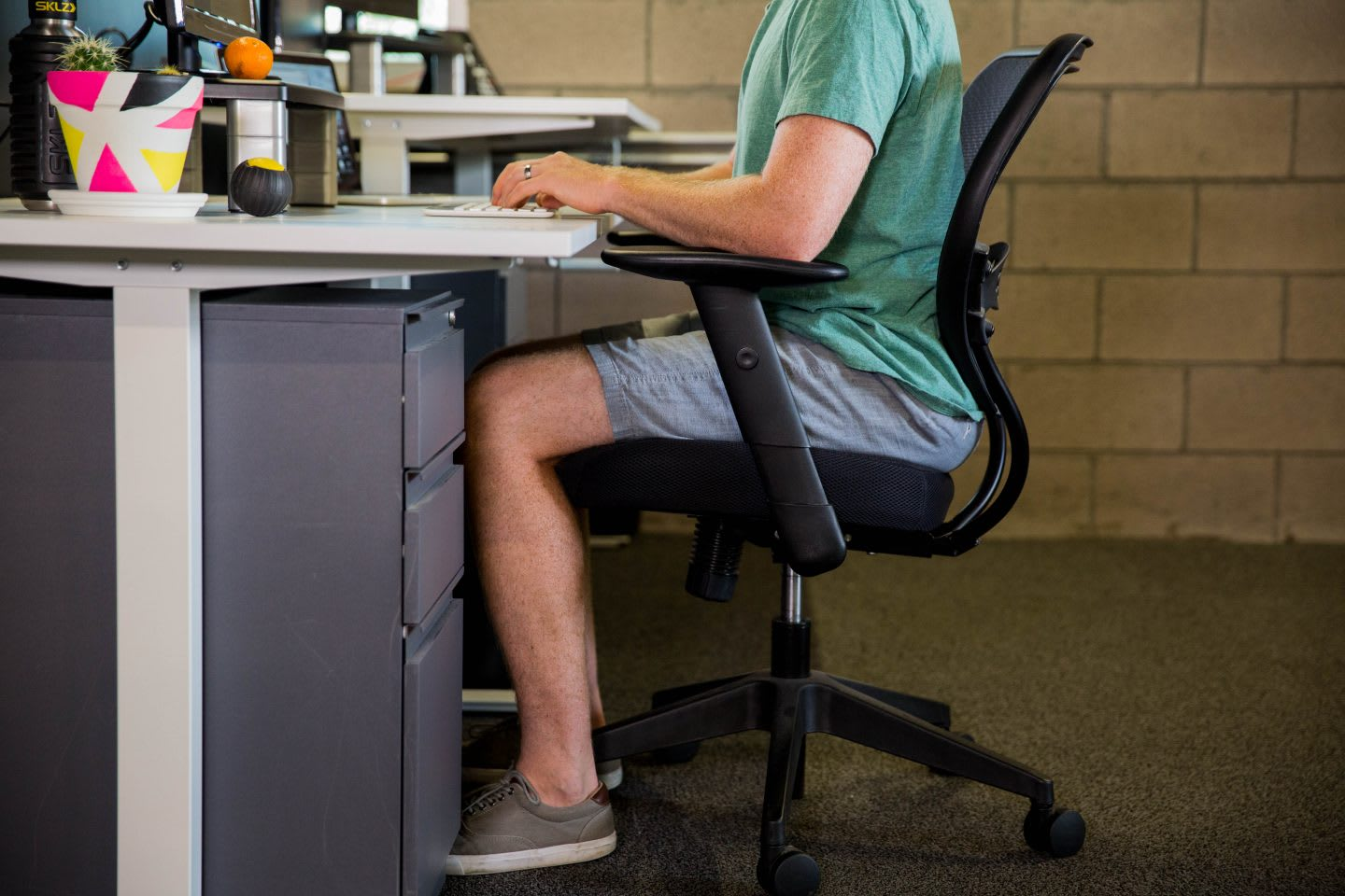 A man sitting at a desk in a healthy sitting position wearing shorts, t-shirt and sneakers. sitting position, health, healthy work place, work space, mental health, productivity, EXOS, GamePlan A