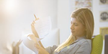 Businesswoman reading at desk in office. health, healthy work place, work space, mental health, productivity, EXOS, GamePlan A