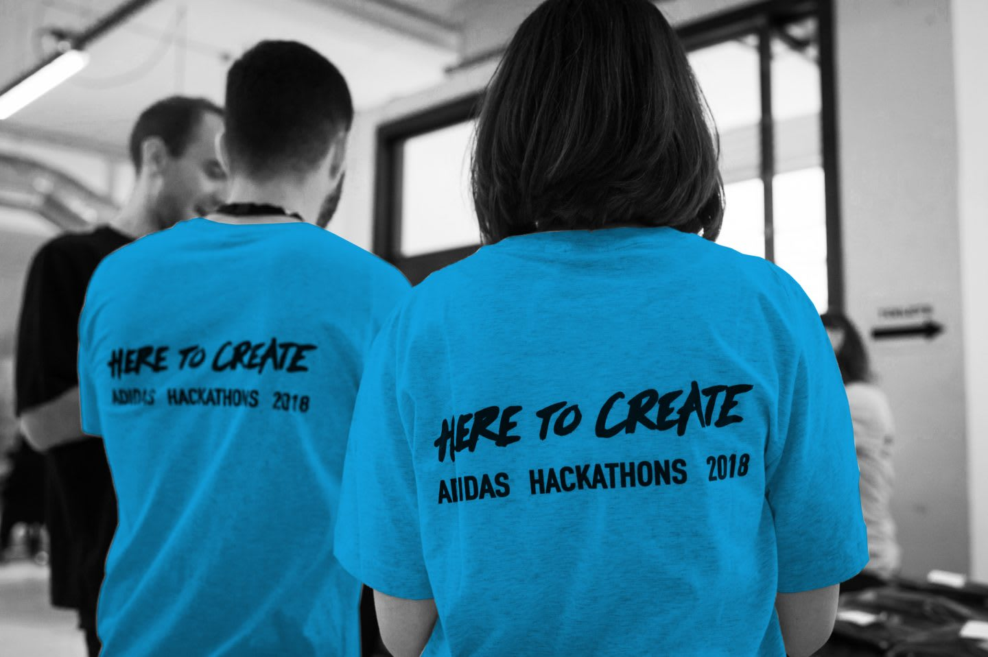 Participants of a Hackathon stand together and discuss their project wearing adidas Hackathon branded t-shirt, digital, ideas, innovation, technology, hackathon, coding, group, teamwork, project, GamePlan A