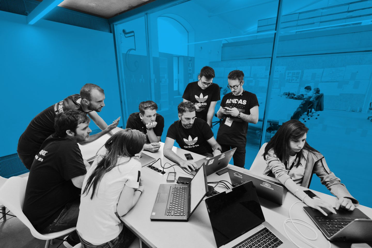 Participants of a Hackathon stand together and discuss their project, digital, ideas, innovation, technology, computers, hackathon, coding, group, teamwork, project, adidas, GamePlan A