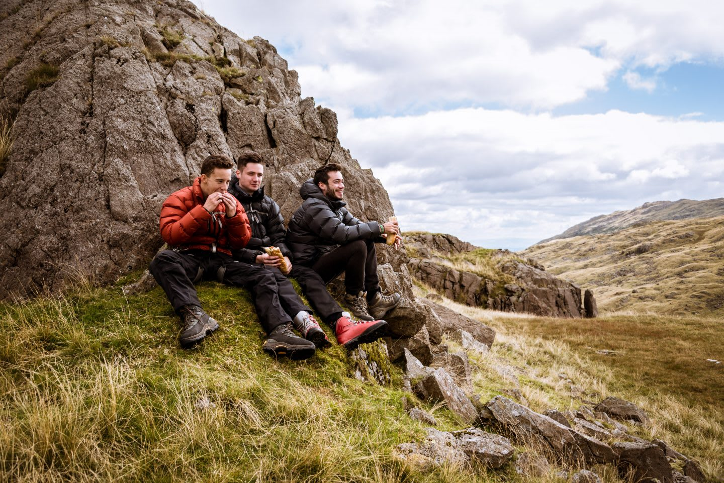 Three young male hiking friends eating sandwiches, The Lake District, Cumbria, UK, nutrition tips, healthy nutrition, fitness, outdoor, hiking, food, GamePlan A