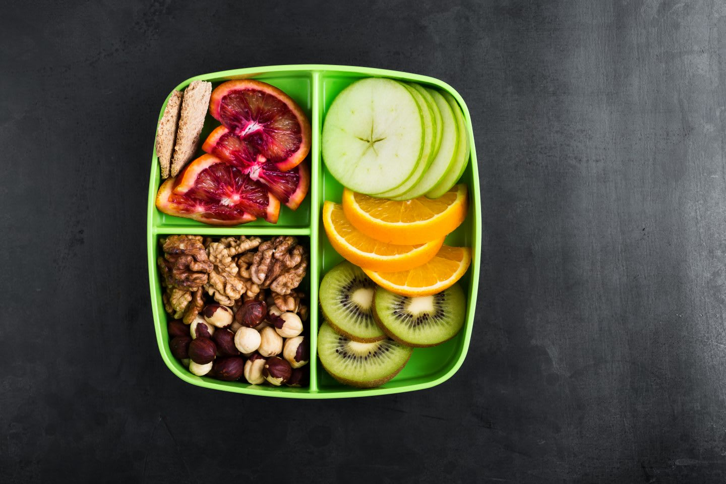Healthy fruits and nuts snack box with oranges, apples, kiwi,walnuts, hazelnuts, and crackers viewed from above. nutrition tips, healthy nutrition, fitness, outdoor, hiking, food, GamePlan A