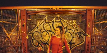 Woman in red adidas sweater pauses after a run and stretches her left quadriceps on Brooklyn Bridge in New York City, sport, running, city run, night run, adidas, boost, headphones, healthy life, GamePlan A