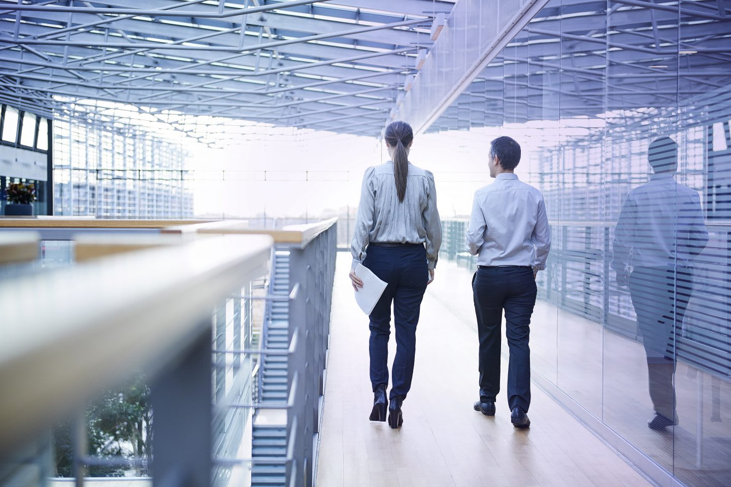 Rear view of businessman and woman walking on office balcony. Mental strength, brainwaves, career, sports, synchronized brains, performance, psychology, research, GamePlan A