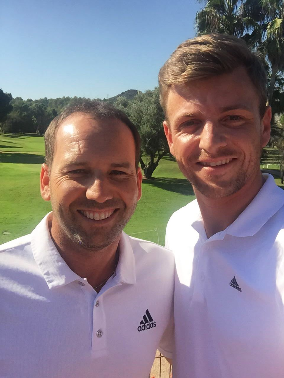 Sergio García and Ben Howlett smiling into the camera at a golf course, golf, golf course, pro athletes, sport, adidas, GamePlan A