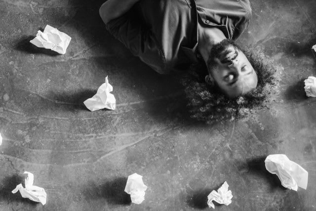 Man lying on the floor after brainstorming surorunded by crinkled balls of paper, failure, frustration, conceptualize, ,ideas, brainstorming, creativity, GamePlan A