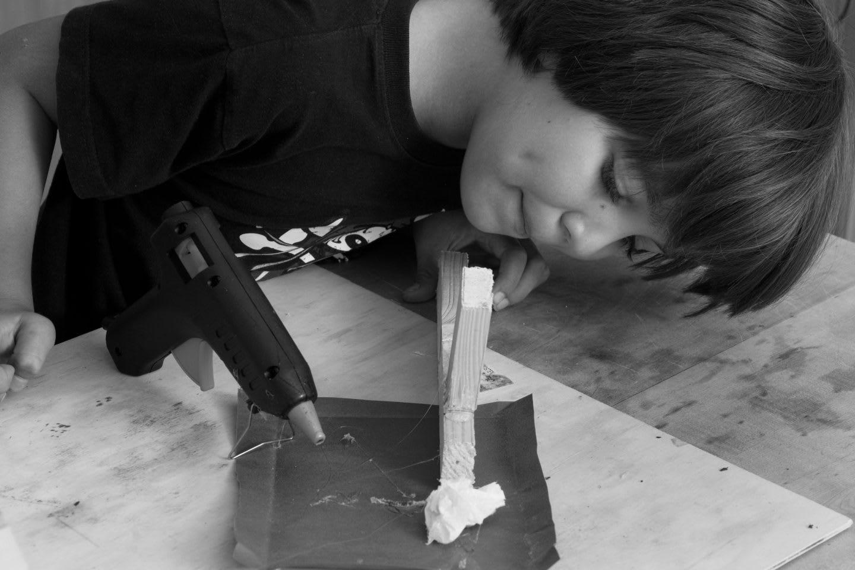 Little Boy using glue gun to stick together wood, creative work, craft, experimenting, creativity, GamePlan A