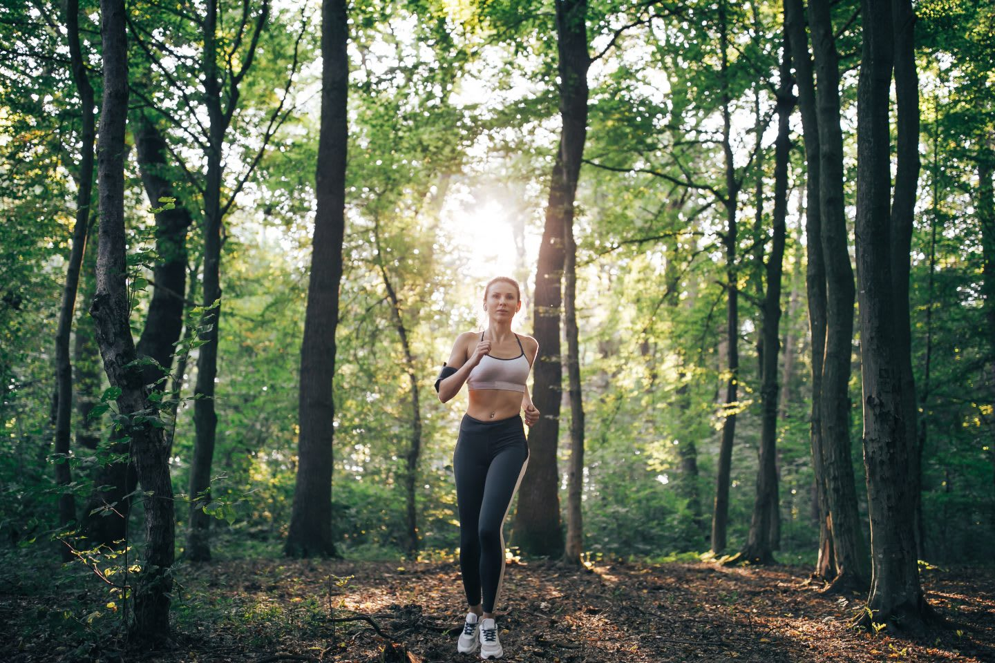 Woman running in a forest with light breaking through trees, morning routine, athletes, running, early morning run, motivation, habits, GamePlan A