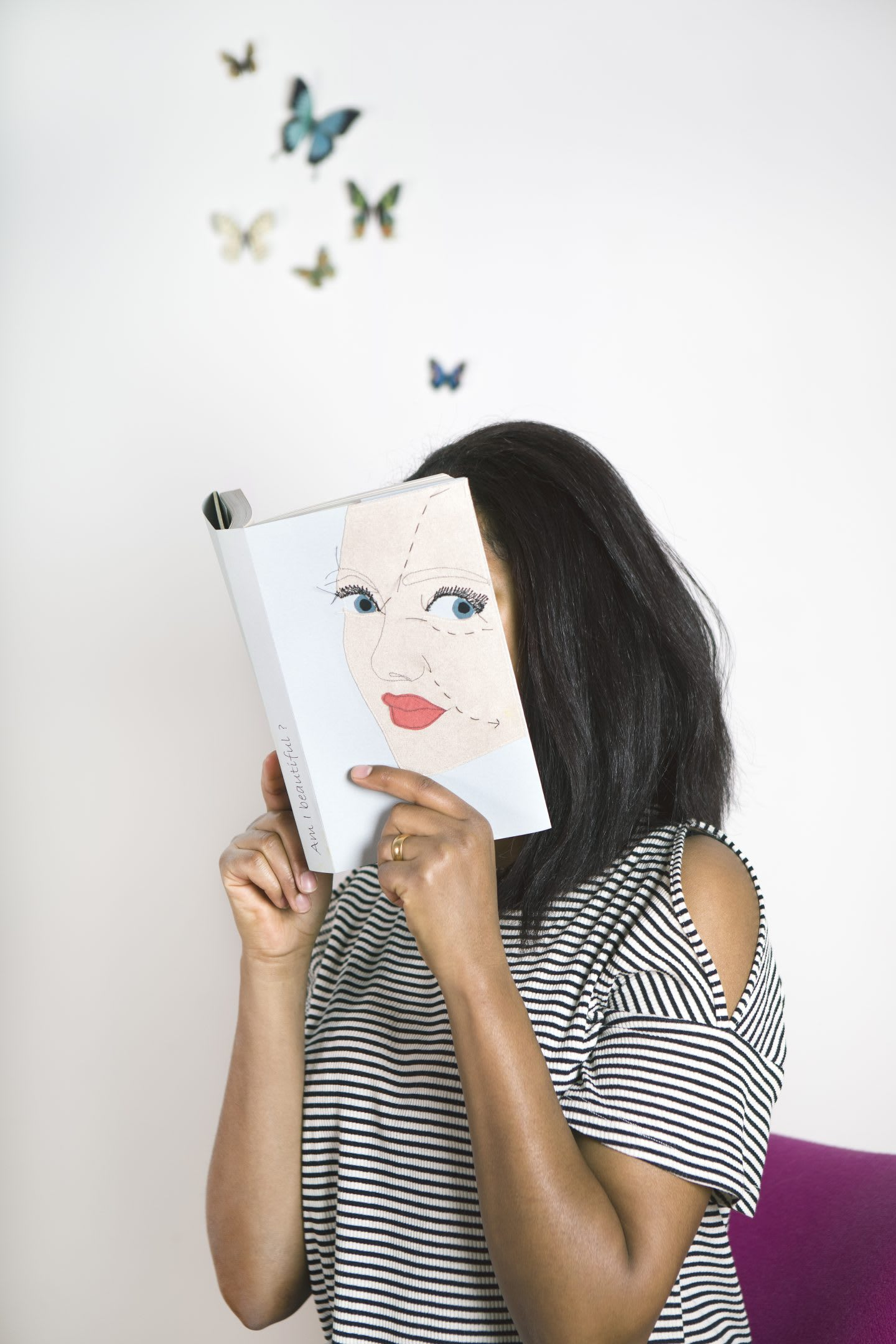 Woman wearing a stripy shirt reading a book with face hidden, imagination, butterflies, thinking, creative, personal, rest, inspiration, GamePlan A