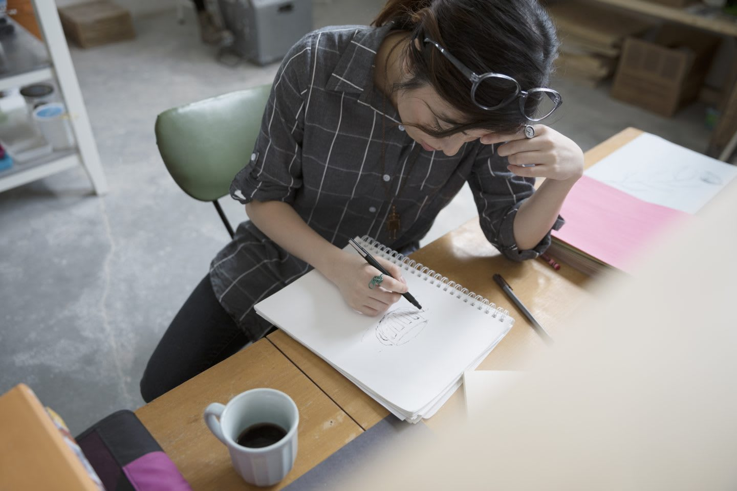 Woman with sunglasses sketching at a desk with concentration, studio, artist, female, coffee cup, notebook, art, focus, creativity, GamePlan A