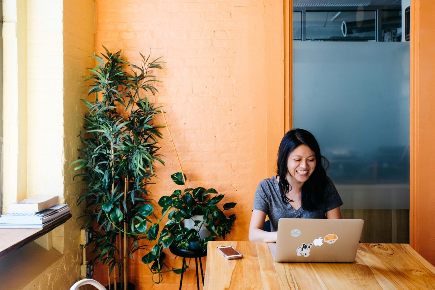 Smiling woman working in cafe with orange walls with laptop surrounded by plants, Georgette Eva, working, happy, inspiration, productivity, new spaces, co-working, GamePlan A