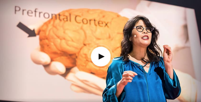 Woman wearing glasses and blue shirt giving a speech on stage in front of picture of brain, TED Talks, headpiece, hand gestures, talk, GamePlan A