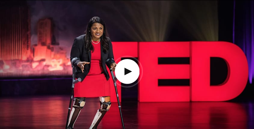 Woman in red dress with prosthetic legs and crutches giving speech on stage in front of red sign, TED Talks, challenges, inspirational, speaker, talk, GamePlan A