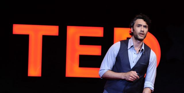 Main in waistcoat giving TED Talks speech on stage in front of red sign, inspiring, thinking, speaking, creative, GamePlan A
