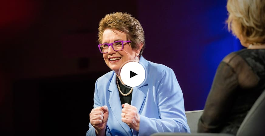 Woman wearing a blue suit and purple glasses smiling while giving talk on stage, Billie Jean King, TED Talks, speaker, talk, inspiration, confidence, challenging status quo, GamePlan A