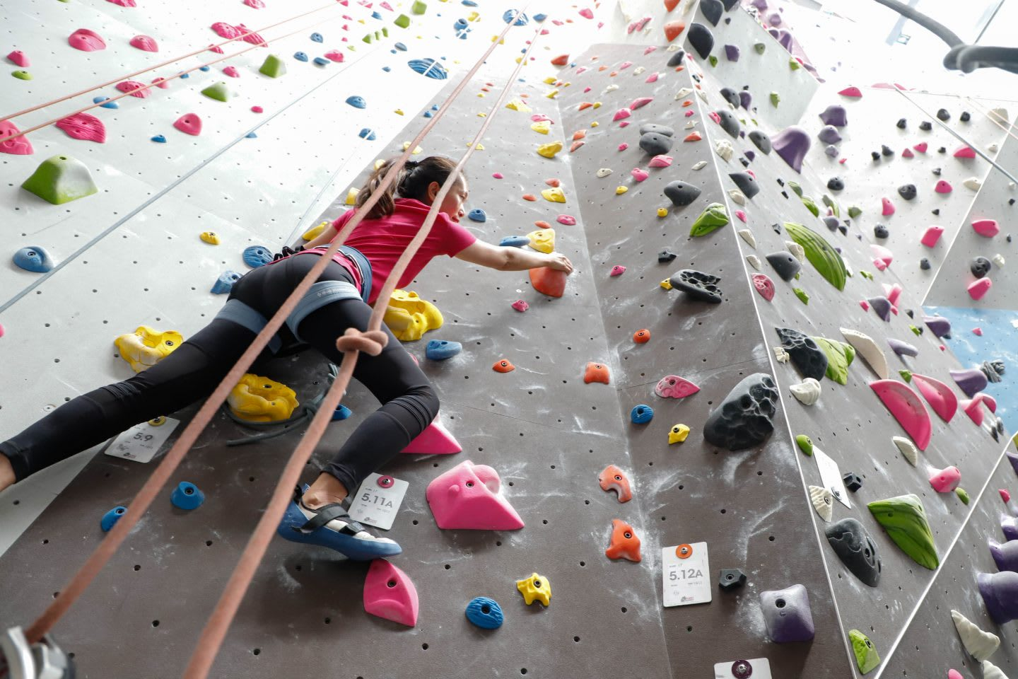 A woman climbing up an indoor climbing wall. challenge, overcoming fears, self-reflection, self-improvement, leadership skills, GamePlan A