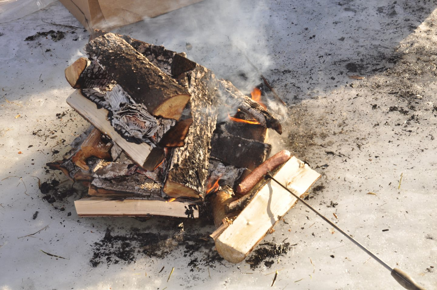 Wood fire on ice with hotdog cooking, roasting, warmth, heat