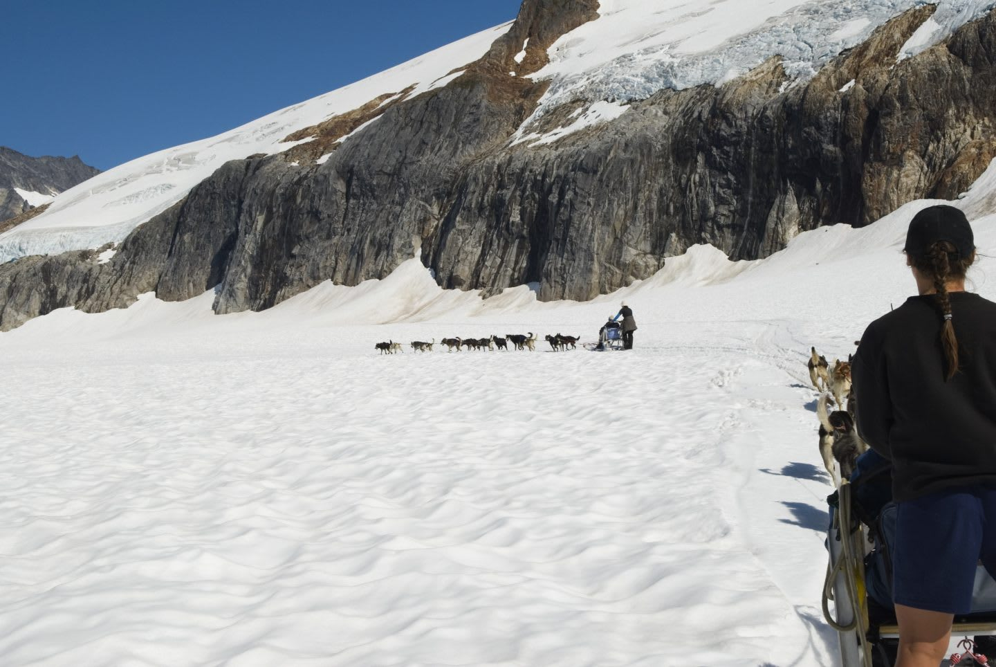 Woman driving a dogsled with another dogsled team on the trail ahead, snow, mountains