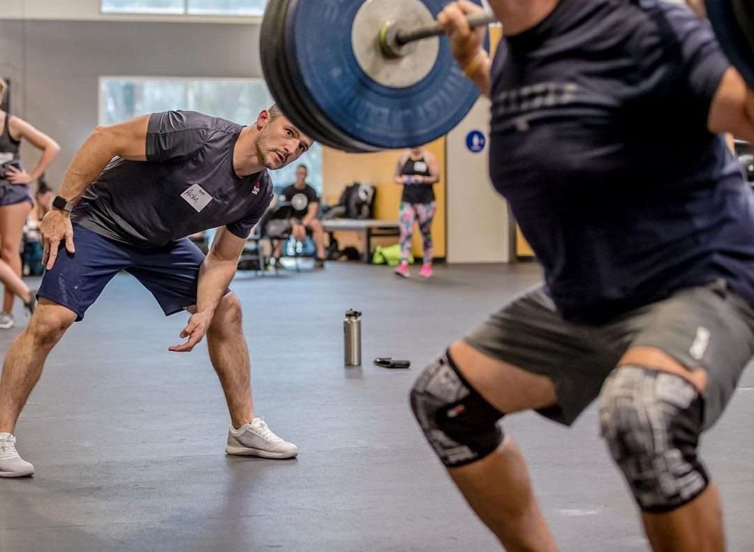 A coach is checking the body position of a weightlifter while lifting in a gym. work-life balance, family, business, productivity, prioritization, fatherhood, career, Reebok, GamePlan A