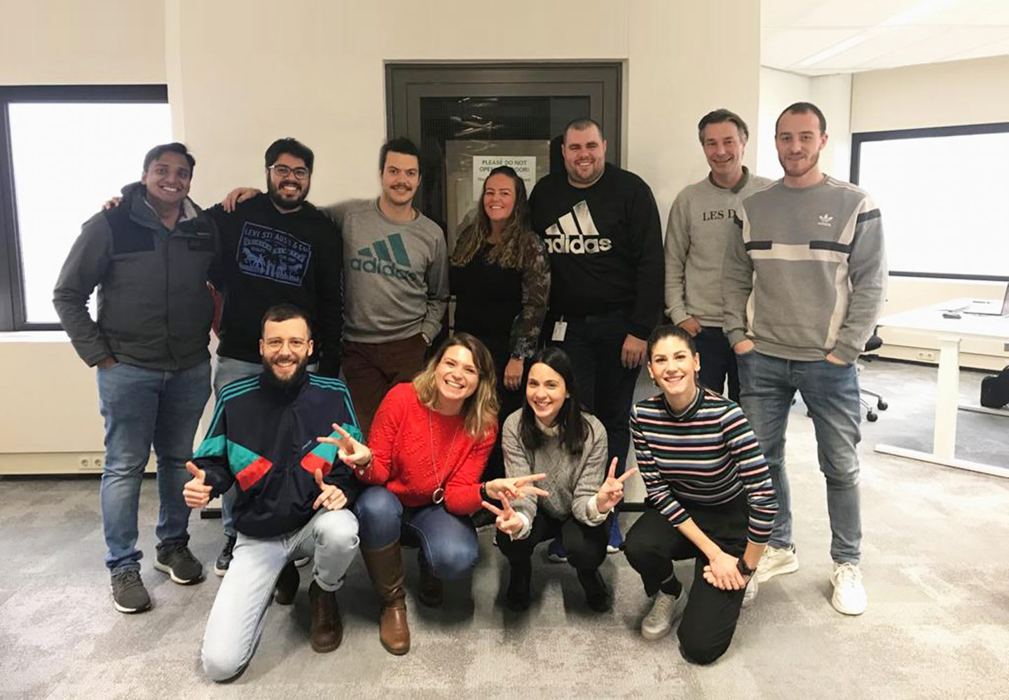A group of young adidas employees posing for a group picture. team, networking, collaboration, confidence, GamePlan A.