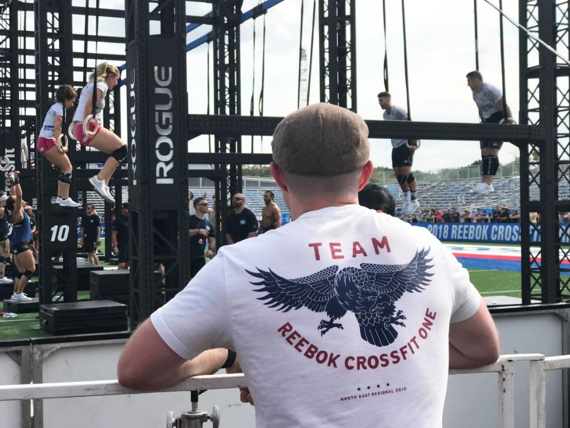 A coach from the back is watching his team doing muscle ups during the Reebok CrossFit Games. leadership, team, teamwork, motivation, success, GamePlan A
