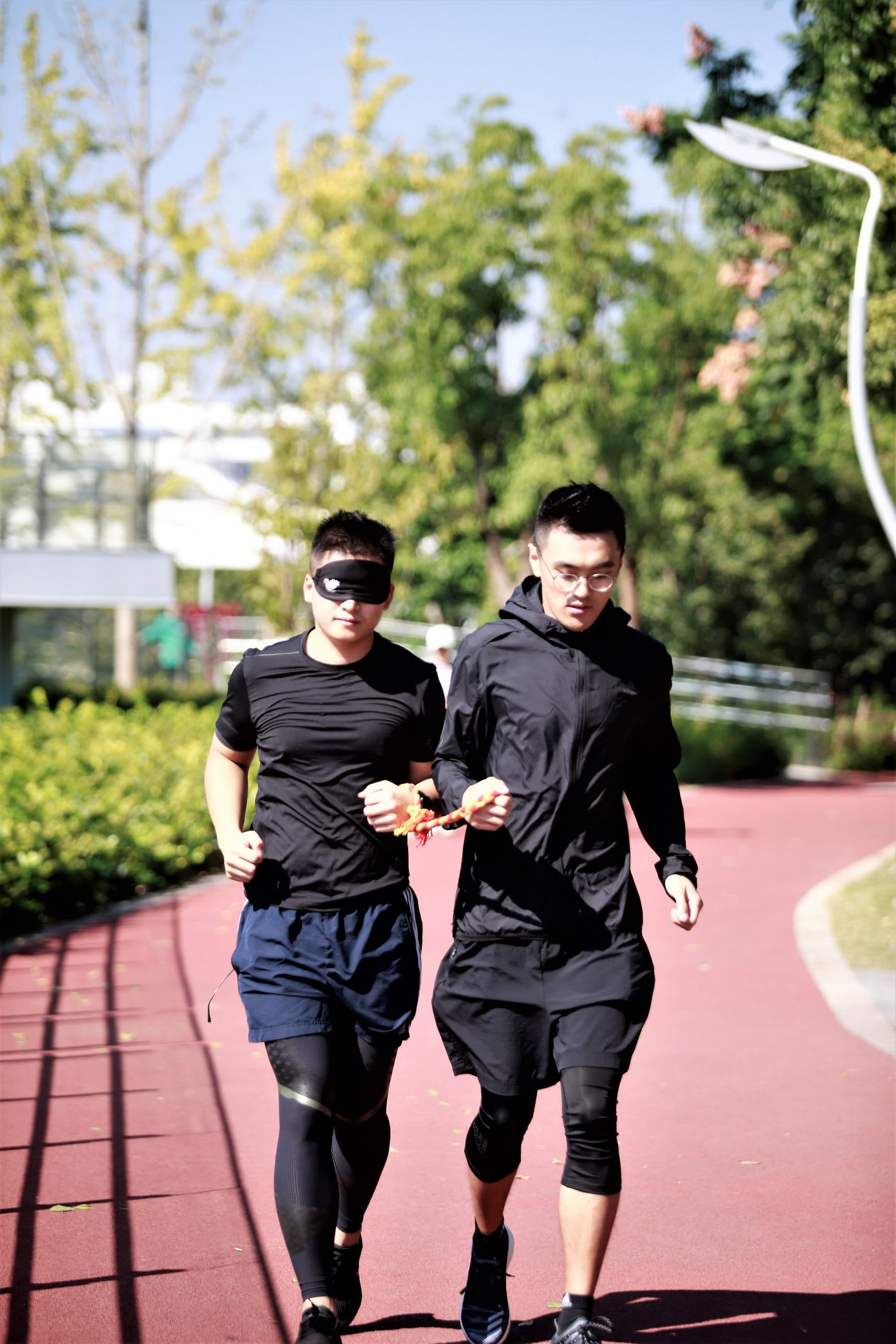 A blind runner and his guide training to run together on the track. guided running, blind running, personal growth, volunteering, GamePlan A.