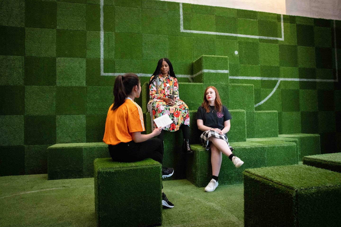 An interview situation in an adidas meeting room, which looks like a football pitch. Three women are chatting with each other. female fan, empowerment, diversity, platform, adidas, football, GamePlan A, SEASON zine
