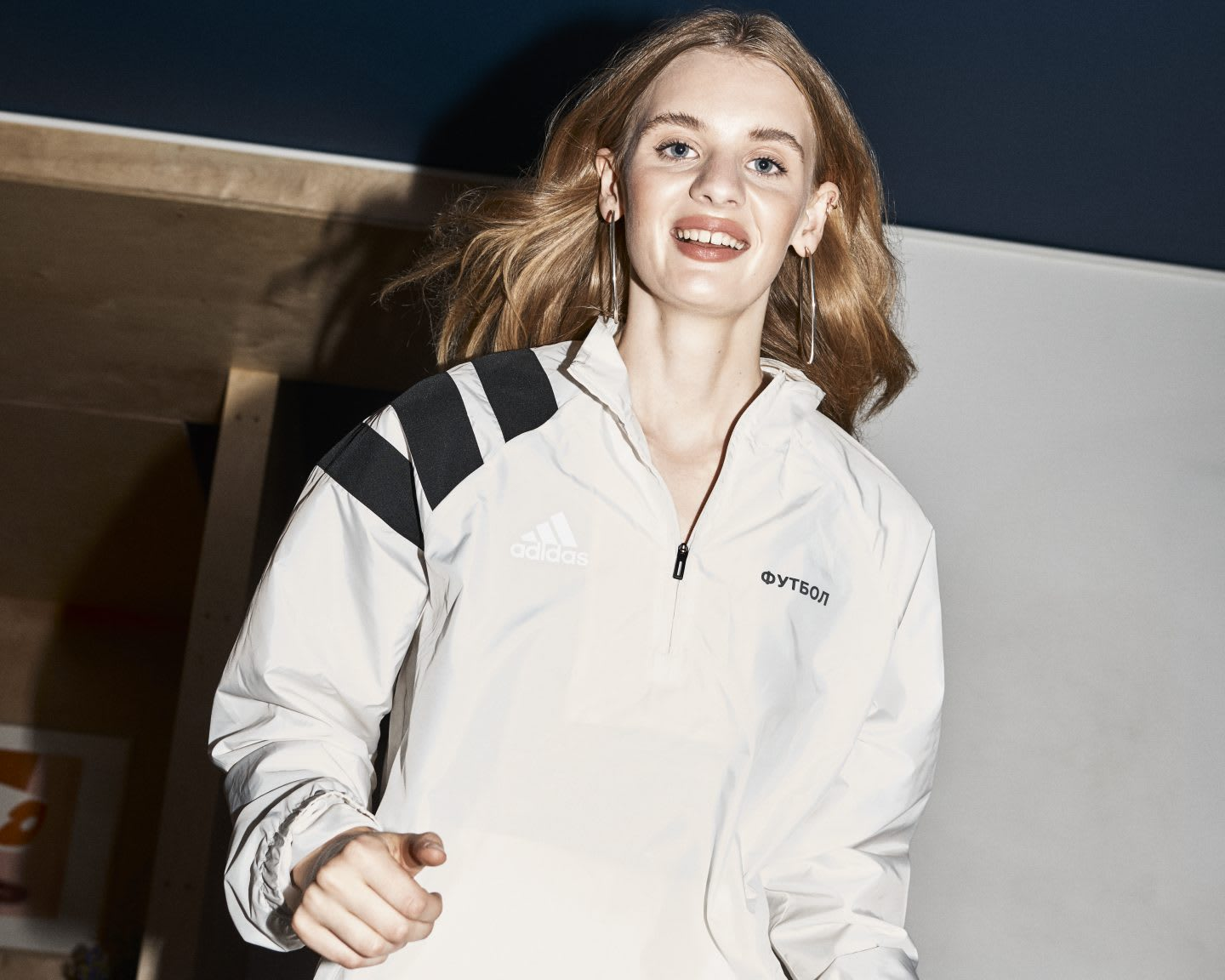 A woman is walking towards the camera with a smile. She is wearing an adidas Football track top. diversity, empowerment, female fan, GamePlan A, SEASON zine