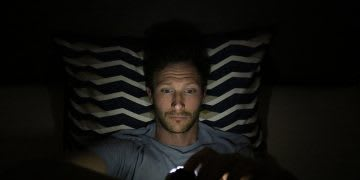 guy lying in bed with the light out but illuminated by the artificial light of his mobile phone in hands. Screen time, bed, sleep, artificial light, GamePlan A