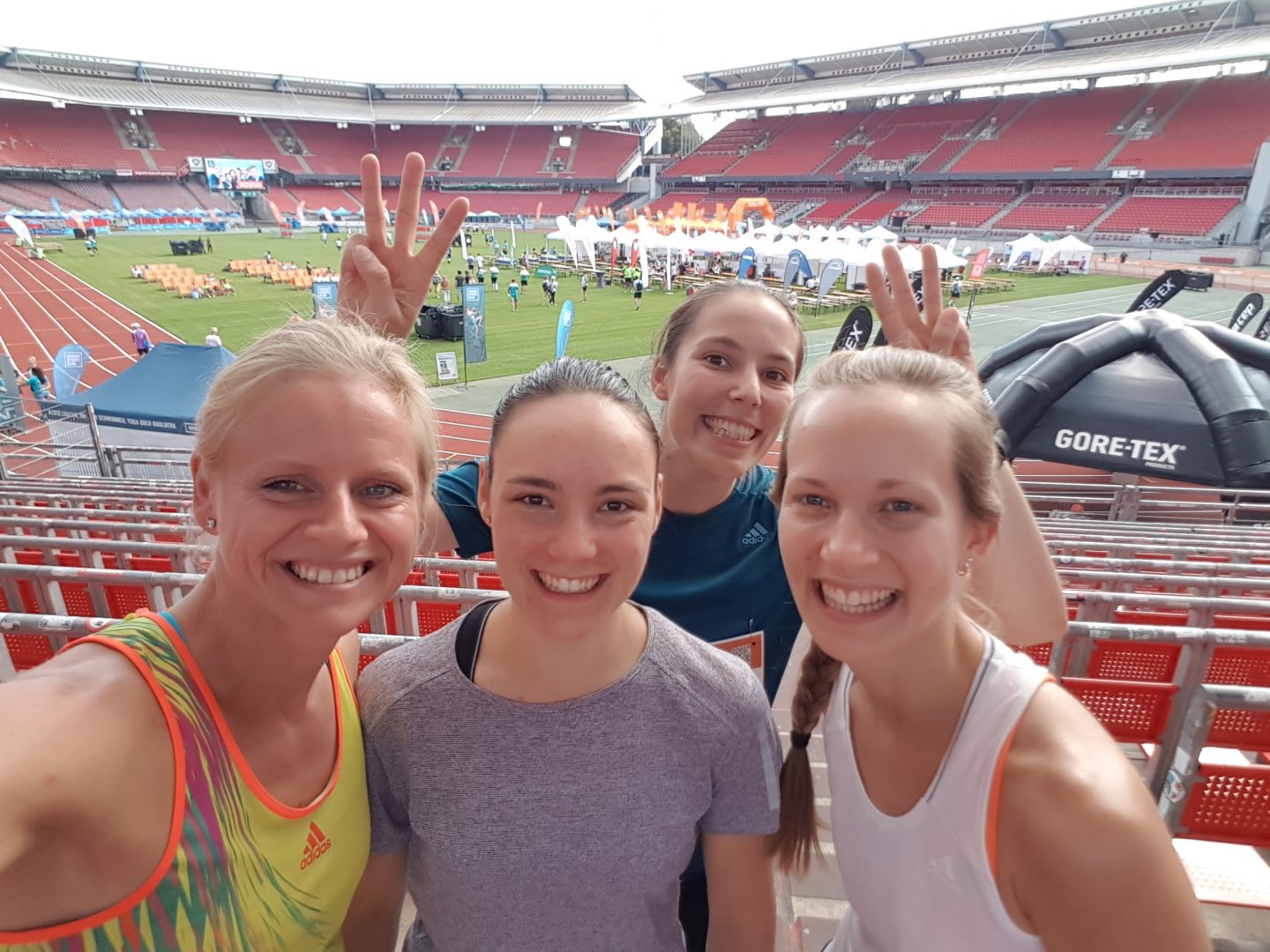 A group of women at a running competition in a stadium. Group running, coaching, performance, company run, track, GamePlan A