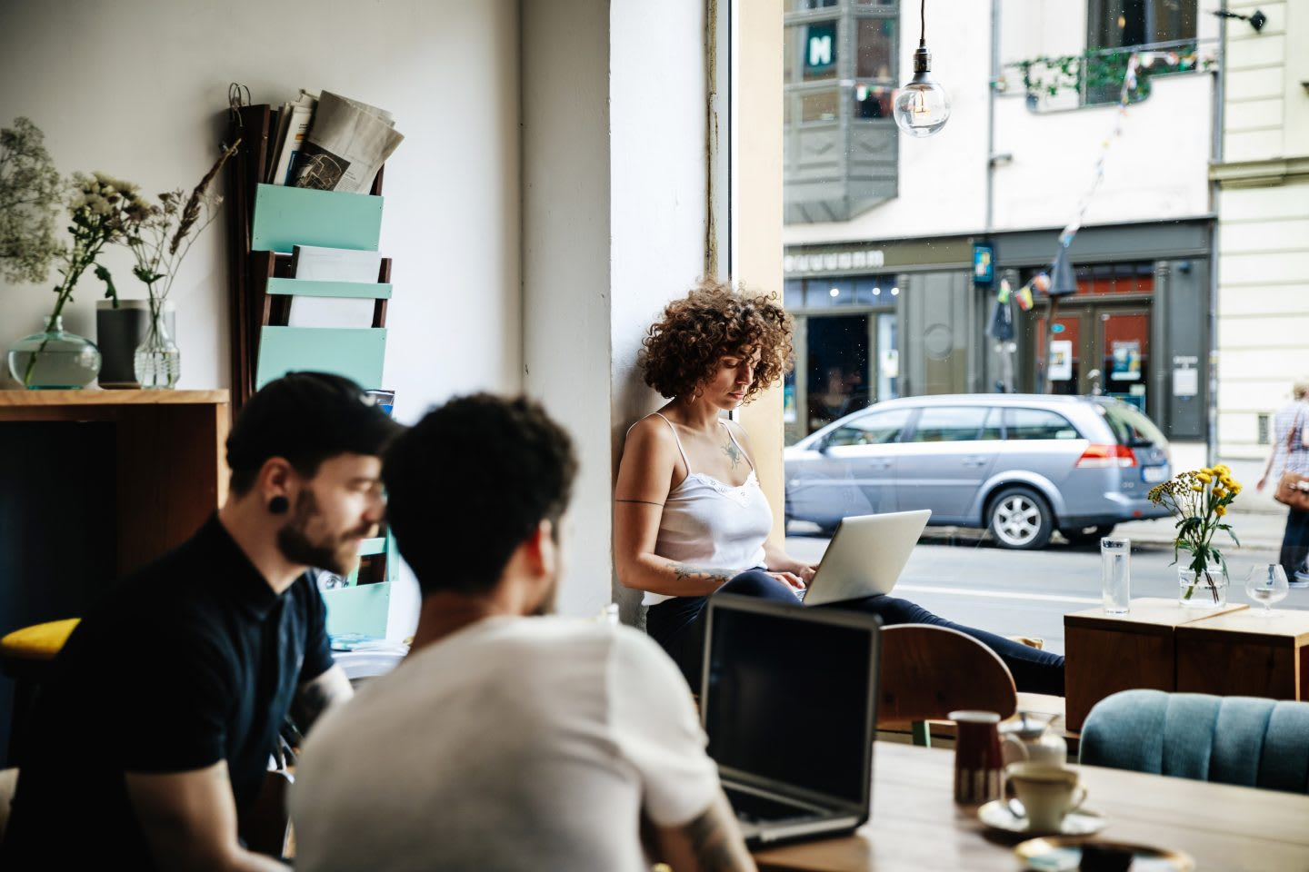A young woman and two men working separately on their laptops at a cafe. quiet, concentration, work environment, flow state, GamePlan A