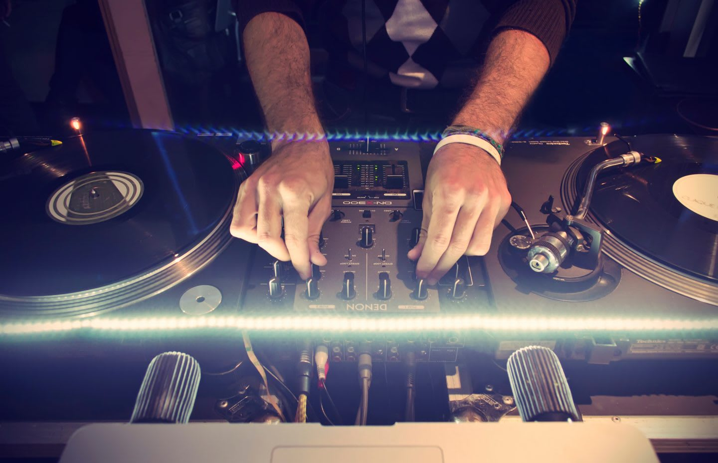 A person producing electronic music at a turntable. mixing music, mood, flow state, GamePlan A