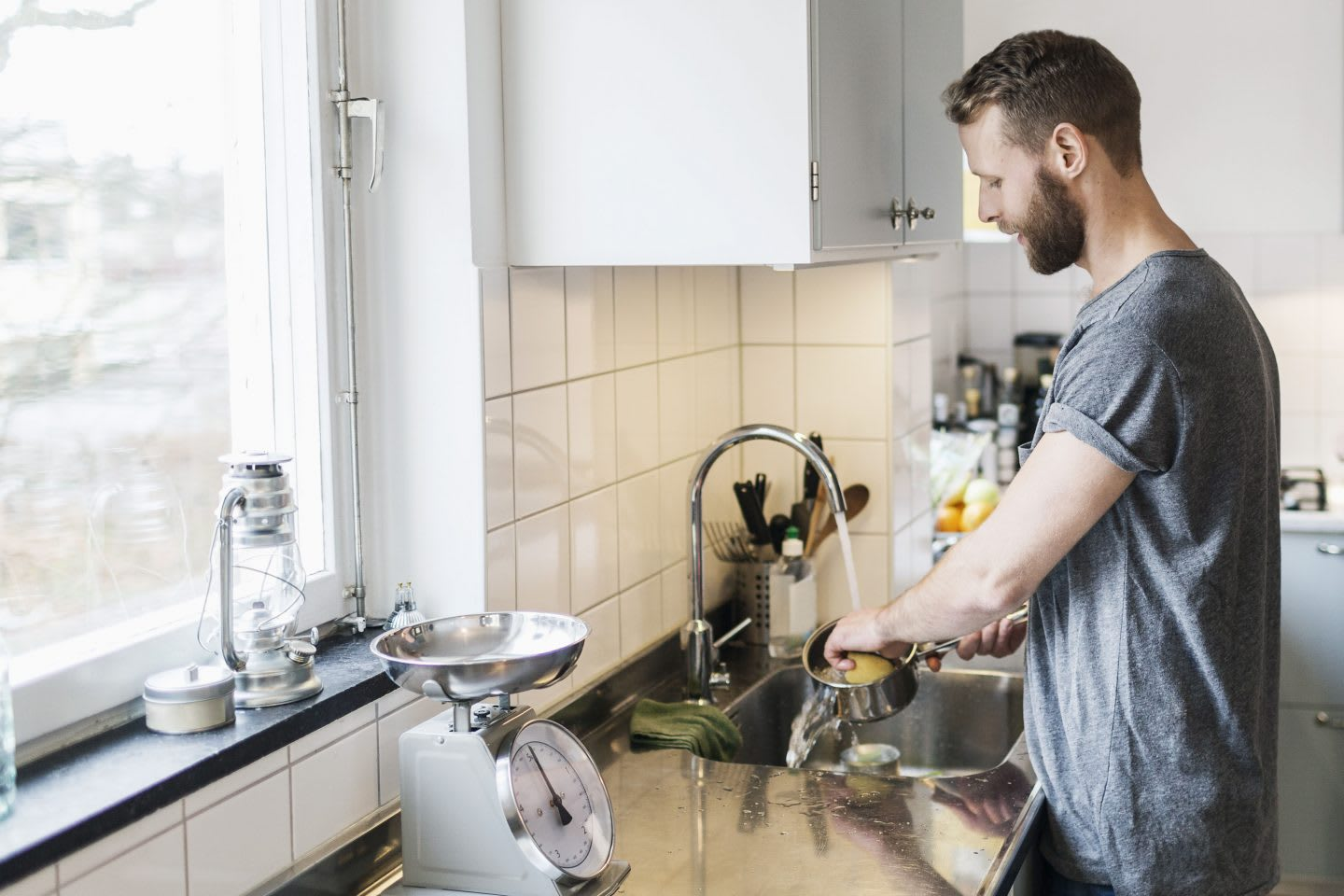 Man washing sauce pan while woman standing in background in kitchen while letting his mind wander. GamePlanA