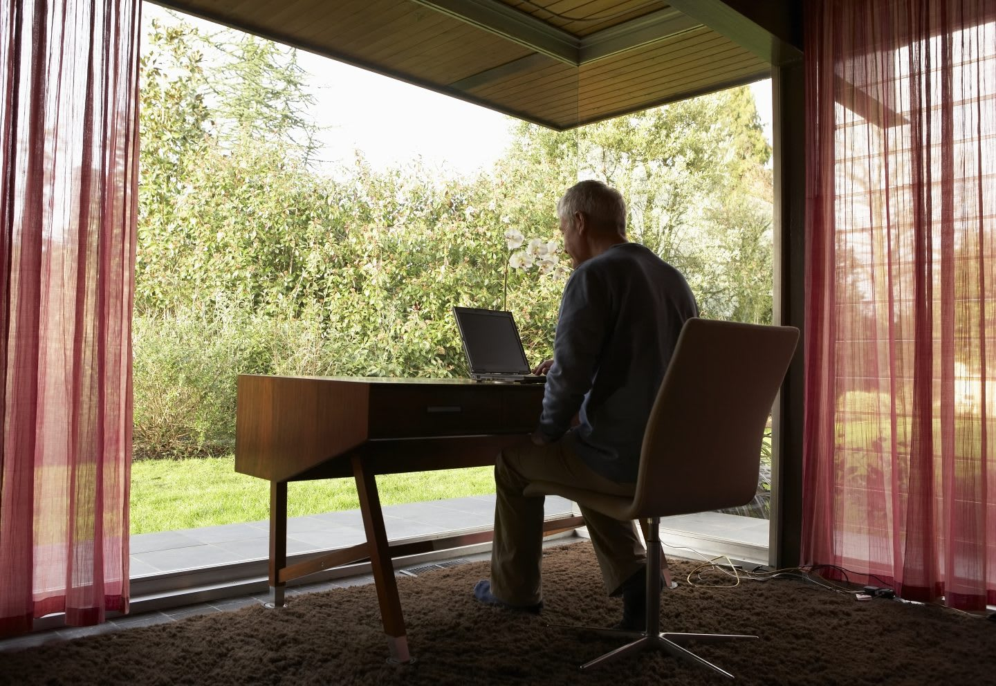 Man working at desk in front of window. The ideal space to let his mind wander.