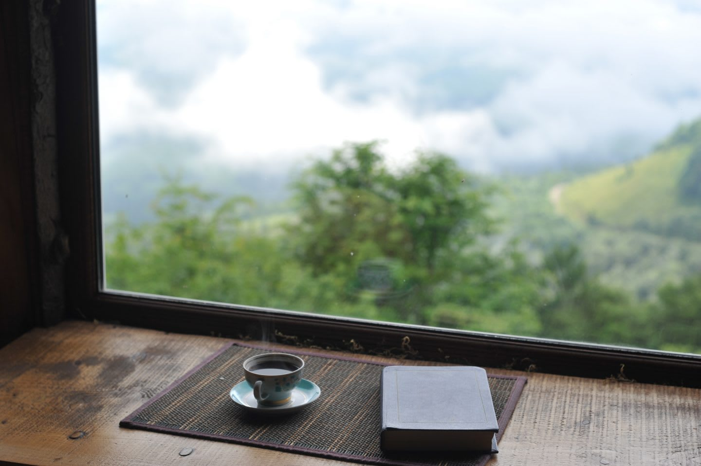 Close-up book and coffee against the beautiful view from the window. Time to let your mind wander. GamePlanA