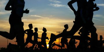 Runners compete race while the sun is setting. Running a Marathon. GamePlanA