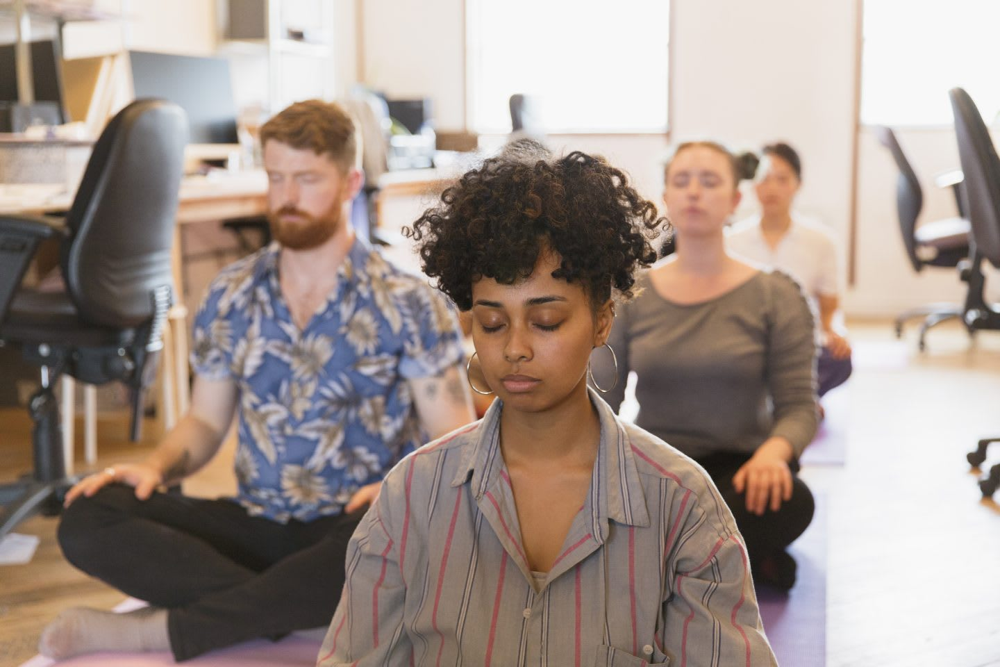 Serene creative business people meditating in office as part of their employer's wellness program