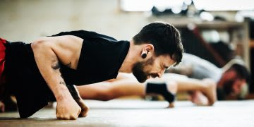 Close-up shot of a muay thai boxing athlete doing pushups in a gym | Key to success