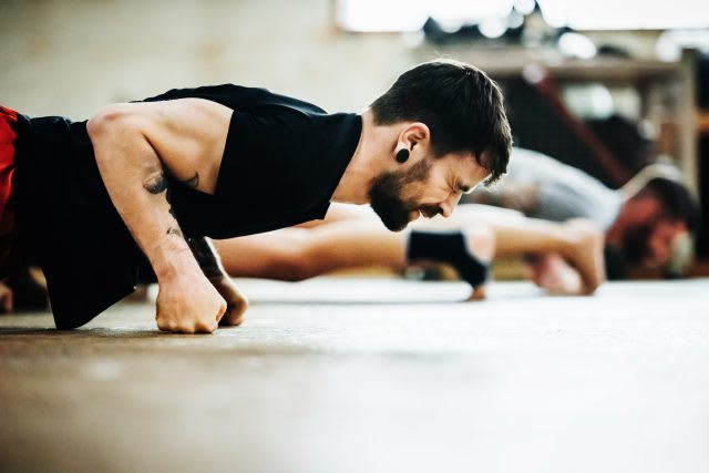 Close-up shot of a muay thai boxing athlete doing pushups in a gym   Key to success