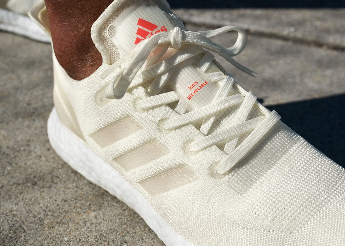 A bright white sneaker with an orange tag on the tongue that reads 100% Recyclable. Sustainable fasion, Gameplan A.