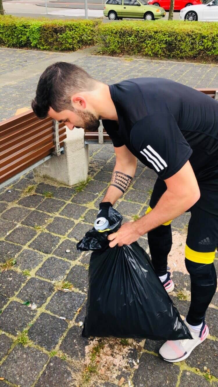 Young man wearing adidas UB19 collecting trash while runnig which is also called plogging
