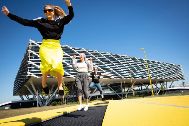 Three girls jumping on the trampoline in front of the adidas Arena building at the World of Sports in HErzogenaurach | Taking a break at work
