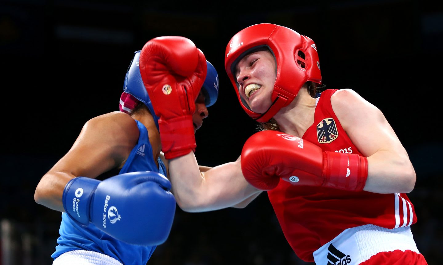 German female boxer Ornella Wahner wears a red headguard and gloves punches towards her opponent with a right uppercut. Gameplan A.