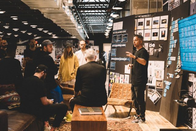 Man presenting to a group of young designers in front of a mood board. business coaching, mindset, performance, GamePlanA